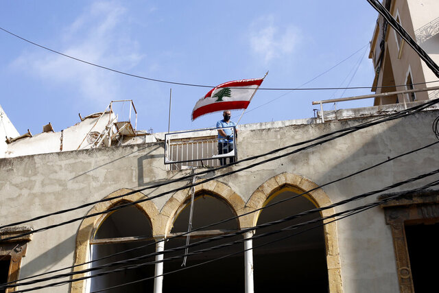 FILE - In this Friday, Aug. 7, 2020, file photo, a man puts a Lebanese flag on the roof of a damaged building at a neighborhood near the scene of an explosion several days earlier that hit the seaport of Beirut, Lebanon.  After a massive explosion ripped through Beirut this month, clinical psychologist Yorgo Younes knew he had to step forward and help his fellow citizens deal with the psychological toll. Online, Younes and others offered to help those grappling with the trauma of a blast that devastated a people already wearied by the coronavirus pandemic and severe economic turmoil. (AP Photo/Thibault Camus, File)