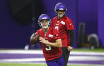 Minnesota Vikings NFL football quarterback Kirk Cousins, right, watches rookie quarterback Jake Browning as he throws during workouts Wednesday, May 22, 2019, in Eagan, Minn. (AP Photo/Jim Mone)