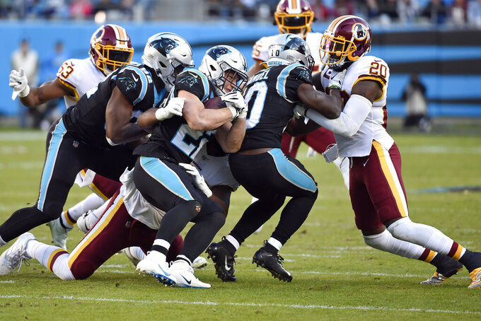 Carolina Panthers defensive tackle Stacy McGee, left, and wide receiver Curtis Samuel (10) block for running back Christian McCaffrey (22) against Washington Redskins strong safety Landon Collins (20) during the second half of an NFL football game in Charlotte, N.C., Sunday, Dec. 1, 2019. (AP Photo/Mike McCarn)