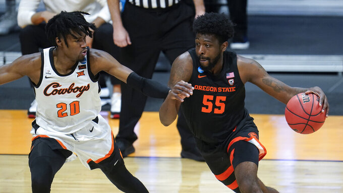 Oregon State guard Tariq Silver (55) drives on Oklahoma State guard Keylan Boone (20) during the first half of a men's college basketball game in the second round of the NCAA tournament at Hinkle Fieldhouse in Indianapolis, Sunday, March 21, 2021. (AP Photo/Paul Sancya)