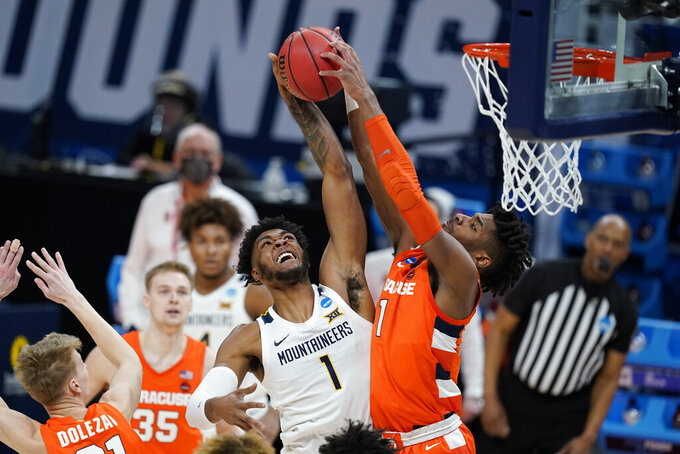 West Virginia's Derek Culver (1) has his shot blocked by Syracuse's Quincy Guerrier (1) during the first half of a second-round game in the NCAA men's college basketball tournament at Bankers Life Fieldhouse, Sunday, March 21, 2021, in Indianapolis. (AP Photo/Darron Cummings)