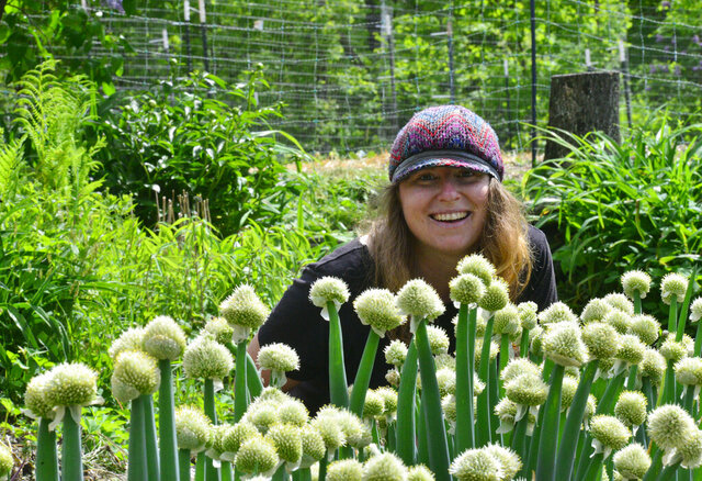 Toni Kessler, owner of West River Seeds, in Townshend, Vt., talks about the Dakota Winter Onions bloom from her garden on Friday, May 29, 2020. (Kristopher Radder/The Brattleboro Reformer via AP)