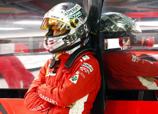 Ferrari's Sebastian Vettel looks on in the garage during the qualifying session of the Singapore Grand Prix