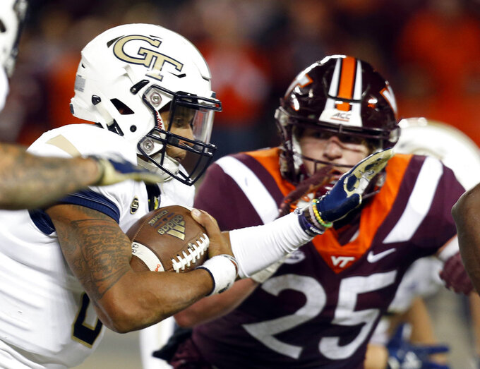 Georgia Tech quarterback Tobias Oliver (8) looks for running room as Virginia Tech linebacker Dax Hollifield (25) pursues during the first half of an NCAA college football game in Blacksburg, Va., Thursday, Oct. 25, 2018. (AP Photo/Steve Helber)