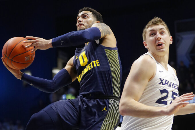 Marquette's Markus Howard (0) shoots next to Xavier's Jason Carter (25) during the first half of an NCAA college basketball game Wednesday, Jan. 29, 2020, in Cincinnati. (AP Photo/John Minchillo)