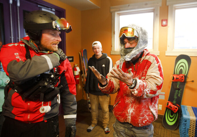 In this Tuesday evening, May 21, 2019 photo, snowboarder John Moser, right, looks at his fingers next to Summit County Rescue Group member Devon Haire after being rescued from out-of-bounds following an avalanche incident at Arapahoe Basin Ski Area, in Dillon, Colo. Moser, who was found by Summit County Rescue Group and the ski patrol, was swept up by an avalanche as he and his friend Patrick Powers were attempting to hike back inbounds. (Hugh Carey/Summit Daily News via AP)