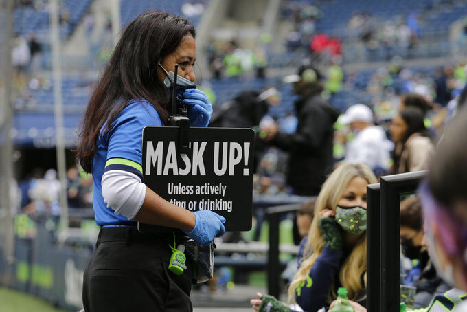 A worker at Lumen Field holds a sign stating the stadium's mask requirement before an NFL football game between the Seattle Seahawks and the Tennessee Titans, Sunday, Sept. 19, 2021, in Seattle. (AP Photo/John Froschauer)