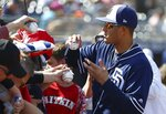 San Diego Padres' Manny Machado gives autographs prior to a spring training baseball game against the Cleveland Indians, Monday, March 4, 2019, in Peoria, Ariz. (AP Photo/Ross D. Franklin)