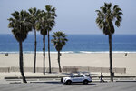 Police patrol the closed-off Santa Monica beach Sunday, March 29, 2020, in Los Angeles. With cases of coronavirus surging and the death toll increasing, lawmakers are pleading with cooped-up Californians to spend a second weekend at home to slow the spread of the infections. (AP Photo/Marcio Jose Sanchez)