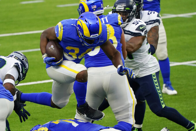 Los Angeles Rams running back Malcolm Brown (34) leaps over an offensive lineman on his way to score a rushing touchdown during the first half of an NFL football game against the Seattle Seahawks Sunday, Nov. 15, 2020, in Inglewood, Calif. (AP Photo/Ashley Landis)