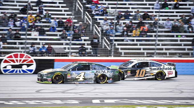 Kevin Harvick (4) and Aric Almirola (10) battle for position during a NASCAR Cup Series auto race at Texas Motor Speedway, Sunday, Nov. 3, 2019, in Fort Worth, Texas. (AP Photo/Larry Papke)