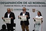 Mexico's President Andres Manuel Lopez Obrador, left, and Deputy Interior Secretary Alejandro Encinas, center, stand with Maria Martinez, mother of Miguel Angel Hernandez Martinez, as they hold cloths embroidered by mothers of some of 43 missing students from the Rural Normal School of Ayotzinapa, with a message reading in Spanish;