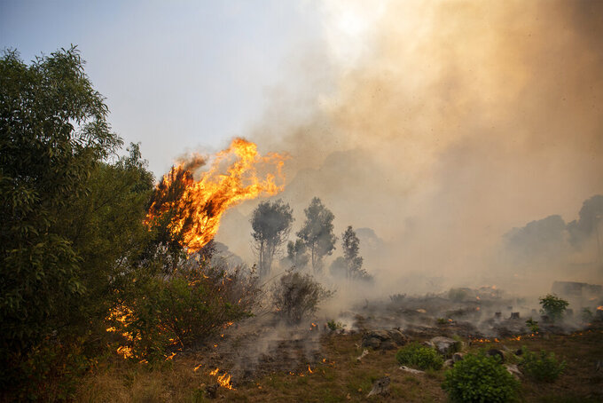 A fire rages out of control on the slopes of Table Mountain in Cape, South Africa, Sunday, April 18, 2021. A wildfire raging on the slopes of the mountain forced the evacuation of students from the University. Of Cape Town. (AP Photo)