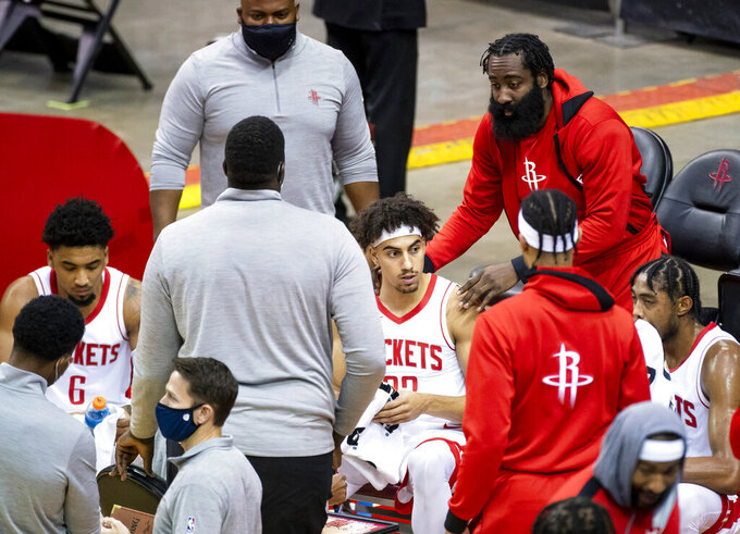 Houston Rockets guard James Harden, top right, joins the huddle while talking to guard Brodric Thomas (33) during the fourth quarter of a preseason NBA basketball game against the San Antonio Spurs, Thursday, Dec. 17, 2020, in Houston. (Mark Mulligan/Houston Chronicle via AP)