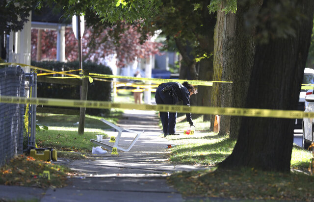 FILE - In this Saturday, Sept. 19, 2020, file photo, a Rochester police technician collects evidence near the home where a fatal house party took place in Rochester, N.Y. Nearly a month after gunshots rang out at a deadly house party at which two teenagers were killed and 14 others were wounded, there have been no arrests, no rewards offered and little word from authorities on where the investigation stands. (Tina MacIntyre-Yee/Democrat & Chronicle via AP)
