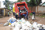 In this photo of Wednesday, July 10, 2019, workers of Kampala Capital City Authority remove garbage under a campaign to encourage people to keep their neighbourhood clean, in Makindye Lukuli area of Kampala, Uganda.  Africa faces a population boom unmatched anywhere in the world, with millions of people moving to fast-growing cities but the decades-old sanitation facilities are crumbling under the pressure. (AP Photo/Ronald Kabuubi)