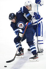Toronto Maple Leafs' Mitchell Marner (16) gets an elbow to the face as Winnipeg Jets' Patrik Laine (29) skates past during third-period NHL hockey game action in Winnipeg, Manitoba, Thursday, Jan. 2, 2020. (John Woods/The Canadian Press via AP)