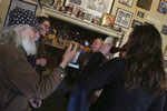 """Patrons have beers at the R and R Bar in Idaho Falls, Idaho, Wednesday, March 25, 2020. Gov. Brad Little issued a stay-home order Wednesday for Idaho residents for the next 21 days. The order requires Idaho's 1.75 million residents to self-isolate at home unless they are healthcare workers, public safety employees or other """"essential workers"""" such as grocery store employees.( John Roark/The Idaho Post-Register via AP)"""