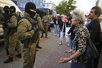 A woman argues with a police officer during an opposition rally to protest the official presidential election results in Minsk, Belarus, Saturday, Sept. 26, 2020. Hundreds of thousands of Belarusians have been protesting daily since the Aug. 9 presidential election. (AP Photo/TUT.by)