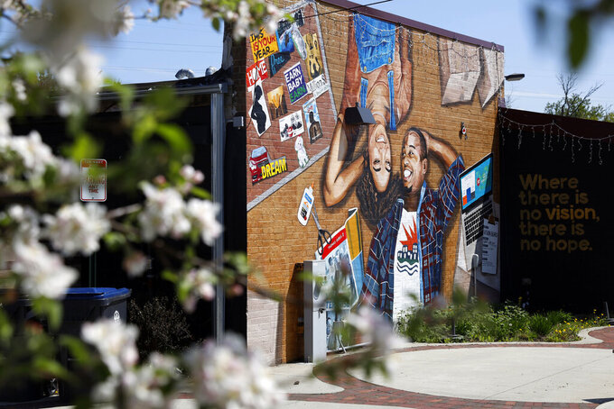 This photo shows a mural painted on the outside wall of Gibbs-Morrison Cultural Center in the 5th Ward of Evanston, Ill., Thursday, April 29, 2021. The Chicago suburb is preparing to pay reparations in the form of housing grants to Black residents who experienced housing discrimination. (AP Photo/Shafkat Anowar)