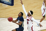 Oral Roberts guard Max Abmas drives to the basket ahead of Arkansas guard Jalen Tate (11) during the first half of a Sweet 16 game in the NCAA men's college basketball tournament at Bankers Life Fieldhouse, Saturday, March 27, 2021, in Indianapolis. (AP Photo/Darron Cummings)