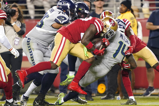 San Francisco 49ers strong safety Jaquiski Tartt, center, strips the ball from Seattle Seahawks wide receiver D.K. Metcalf (14) during the first half of an NFL football game in Santa Clara, Calif., Monday, Nov. 11, 2019. (AP Photo/Tony Avelar)