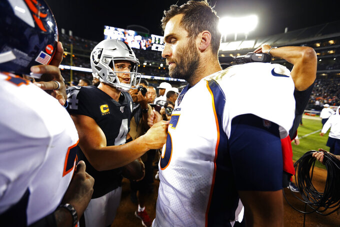 Denver Broncos quarterback Joe Flacco, right, is met by Oakland Raiders quarterback Derek Carr at the end of an NFL football game Monday, Sept. 9, 2019, in Oakland, Calif. Oakland won the game 24-16. (AP Photo/D. Ross Cameron)