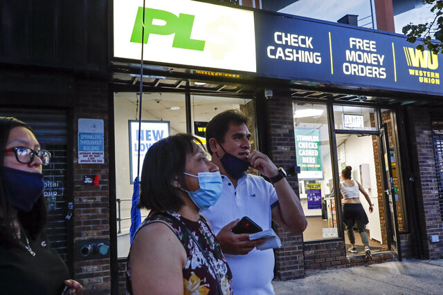 Magnolia Ortega, center, stands outside a Western Union with her husband Arturo Morales and their daughter Marlene after wiring money to her family in Mexico, Wednesday, June 24, 2020, in Staten Island, New York. Ortega lost her job cleaning houses amid the COVID-19 pandemic, reducing the monthly amount she sends home. She's considering returning to her hometown of San Jeronimo Xayacatlan but says there's no work there either and that would mean one less family member sending back one less monthly check. (AP Photo/John Minchillo)