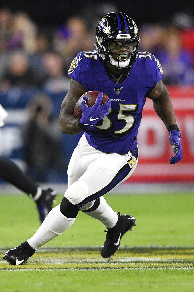 Baltimore Ravens running back Gus Edwards (35) runs against the Tennessee Titans during the first half an NFL divisional playoff football game, Saturday, Jan. 11, 2020, in Baltimore. (AP Photo/Nick Wass)