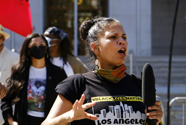 FILE - In this Aug. 5, 2020 file photo, Melina Abdullah speaks during a Black Lives Matter protest at the Hall of Justice in downtown Los Angeles. Los Angeles police are investigating a possible hoax call that led to the department's SWAT team responding on the block of one of the city's leading Black Lives Matter activists. Abdullah, co-founder of BLM-LA, streamed live video on Instagram, showing armed officers outside her house. The video showed officers screaming orders at her when she came outside. Nobody was hurt. (AP Photo/Richard Vogel, File)