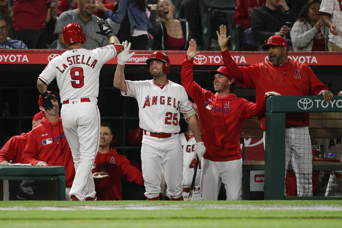 Los Angeles Angels' Tommy La Stella, left, high-fives teammates to celebrate his home run during the fourth inning of a baseball game against the Milwaukee Brewers, Tuesday, April 9, 2019, in Anaheim, Calif. (AP Photo/Jae C. Hong)