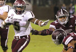 Texas A&M running back Trayveon Williams (5) stiff-arms Mississippi State safety Mark McLaurin (41) and defensive tackle Jeffery Simmons (94) during the second half of their NCAA college football game on Saturday, Oct. 27, 2018, in Starkville, Miss. MSU won 28-13. (AP Photo/Jim Lytle)