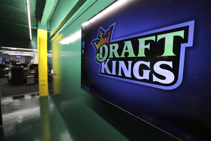 "FILE - In this May 2, 2019, file photo, the DraftKings logo is displayed at the sports betting company headquarters in Boston. Sports gambling giant DraftKings won't give a former ""Bachelor"" contestant the $1 million prize for winning an online fantasy football contest after she and her husband were accused of cheating.Jade Roper-Tolbert beat more than 100,000 entries to take the top prize, but some in the fantasy sports community were quick to allege she coordinated with her husband, Tanner Tolbert, to submit more than the maximum 150 entries. Roper-Tolbert was no longer listed as the winner Saturday. A DraftKings statement says the company decided to update the standings for several contests and did not elaborate. (AP Photo/Charles Krupa, File)"
