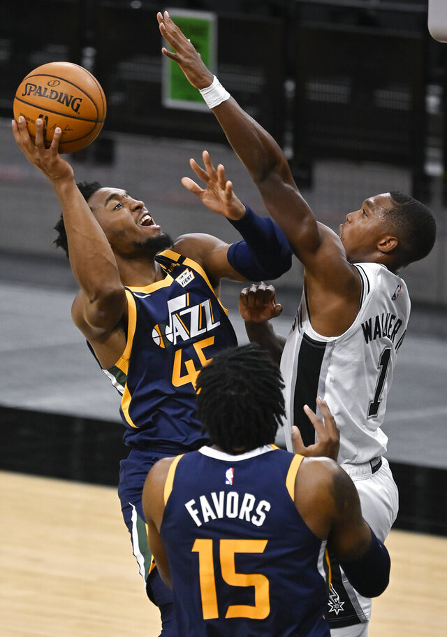 Utah Jazz's Donovan Mitchell (45) shoots against San Antonio Spurs' Lonnie Walker IV (1) as Jazz forward Derrick Favors looks on during the first half of an NBA basketball game, Sunday, Jan. 3, 2021, in San Antonio. (AP Photo/Darren Abate)