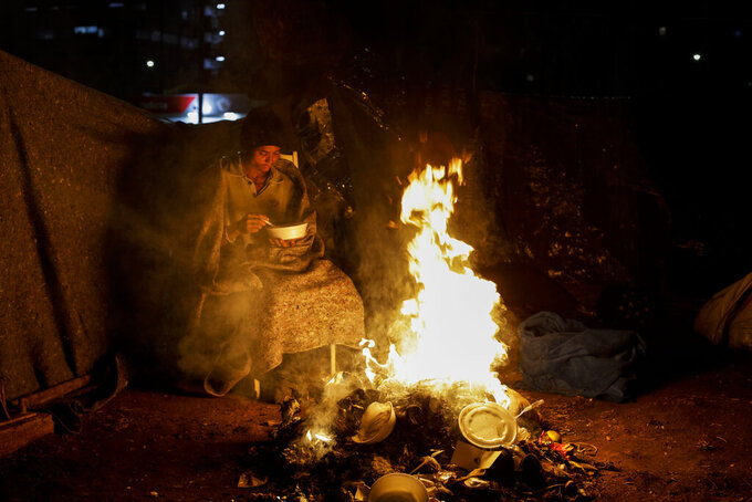 A homeless person sits by a fire amid historically cold weather in Sao Paulo, Brazil, late Thursday, July 29, 2021. The Brazilian government's meteorological institute says low temperatures should endure until the start of August. (AP Photo/Marcelo Chello)
