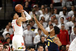 Maryland guard Anthony Cowan Jr. (1) shoots next to Michigan guard David DeJulius (0) during the first half of an NCAA college basketball game, Sunday, March 8, 2020, in College Park, Md. (AP Photo/Nick Wass)