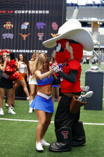 Kansas cheerleader Darian Bruch dances a two-step with Texas Tech mascot Raider Red backstage on the first day of Big 12 Conference NCAA college football media days Monday, July 15, 2019, at AT&T Stadium in Arlington, Texas. (AP Photo/David Kent)