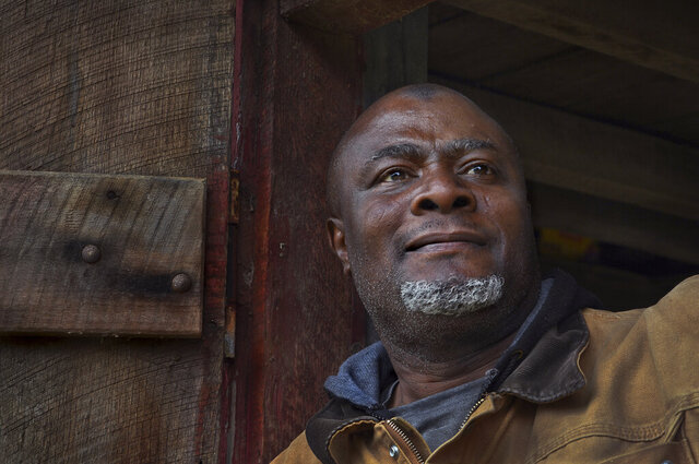 This photo taken Jan. 13, 2020, shows  Olaniyi Balogun peering out at the land he farms from the doorway of a work shed in Brookeville, MD. Balogun is a native of Nigeria who farms cabbage, kale, broccoli, Brussels sprouts and collard greens on Agricultural Reserve land near Brookeville. As Montgomery county's demographics change, more immigrants are seeking land in the agricultural reserve to farm and rear animals, often bringing crops and farming practices from their home countries. The program connects landowners with aspiring farmers who cannot afford to buy their own land. (Michael S. Williamson/The Washington Post via AP)