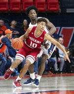 Indiana guard Rob Phinisee protects the ball from the defense of Illinois guard Andres Feliz, rear, during the first half of an NCAA college basketball game in Champaign, Ill., Thursday, March 7, 2019. (AP Photo/Stephen Haas)
