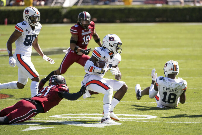 Auburn wide receiver Eli Stove (12) runs with the ball against South Carolina defensive back Shilo Sanders (21) during the first half of an NCAA college football game Saturday, Oct. 17, 2020, in Columbia, S.C. (AP Photo/Sean Rayford)