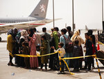 In this photo provided by the U.S. Marine Corps, civilians prepare to board a plane during an evacuation at Hamid Karzai International Airport, Kabul, Afghanistan, Wednesday, Aug. 18, 2021. (Staff Sgt. Victor Mancilla/U.S. Marine Corps  via AP)