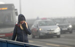 A girl walks across a bridge in Belgrade, Serbia, Wednesday, Jan. 15, 2020. Cities throughout the Balkans have been hit by dangerous levels of air pollution in recent days, prompting residents' anger and government warnings to stay indoors and avoid physical activity. (AP Photo/Darko Vojinovic)