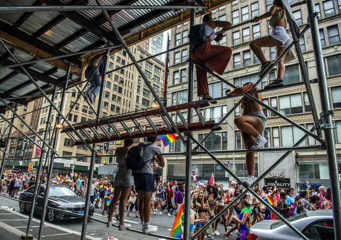 People climb the railings of scaffolding to get a better view of the Queer Liberation March on Sunday, June 27, 2021, in New York. (AP Photo/Brittainy Newman)
