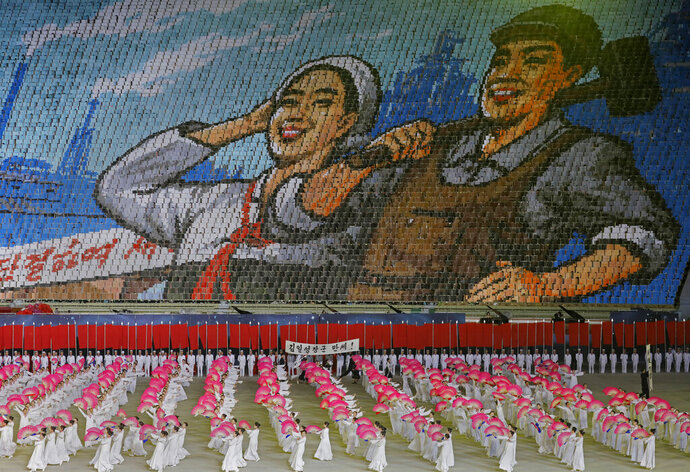 In this Tuesday, July 16, 2019, photo, North Koreans hold cards to make an image depicting a worker and a farmer during a mass game performance of