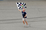 Kevin Harvick's son, Keelan, runs with the winners flag after a NASCAR Cup Series auto race at Michigan International Speedway in Brooklyn, Mich., Sunday, Aug. 11, 2019. (AP Photo/Paul Sancya)