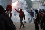 A demonstrator holds a flare during a march against police brutality and racism in Paris, France, Saturday, June 13, 2020, organized by supporters of Adama Traore, who died in police custody in 2016 in circumstances that remain unclear despite four years of back-and-forth autopsies. The march is expected to be the biggest of several demonstrations Saturday inspired by the Black Lives Matter movement in the U.S., and French police ordered the closure of freshly reopened restaurants and shops along the route fearing possible violence. (AP Photo/Thibault Camus)