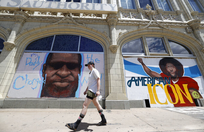 A pedestrian passes murals to honor George Floyd and former NFL quarterback Colin Kaepernick covering pieces of plywood used to shield windows in an empty storefront south of the State Capitol Thursday, June 11, 2020, in Denver. (AP Photo/David Zalubowski)