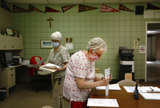Guidance secretary Marge Berckmiller, left, and Sister Bridget Reilly, director of guidance, prepare student transcripts to send to other schools after the closure of Quigley Catholic High School in Baden, Pa., Monday, June 8, 2020. The staff learned of the closure May 29 via videoconference. (AP Photo/ Jessie Wardarski)