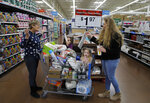 FILE - In this Nov. 27, 2019, file photo from left, Tina Fausto, left, and Olivia Wirtshafter, right, shop with Lilly Flores, second from left, and Laly Rose Stanton the day before the Thanksgiving holiday at a Walmart Supercenter in Las Vegas. On Wednesday, Dec. 11, the Labor Department reports on U.S. consumer prices for November. (AP Photo/John Locher, File)