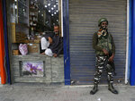 An Indian paramilitary soldier guards as a Kashmiri shopkeeper waits for customers in Srinagar, Indian controlled Kashmir, Monday, July 1, 2019. Thousands of Hindu pilgrims began the arduous trek to an icy Himalayan cave in disputed Kashmir on Monday, with tens of thousands of Indian government forces guarding roads and mountain passes. (AP Photo/Mukhtar Khan)
